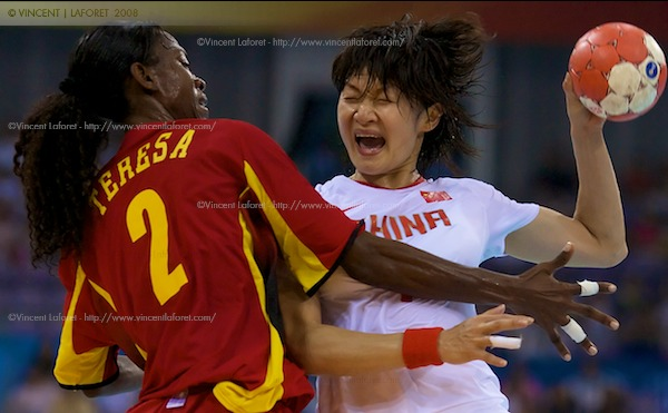 Xiao Mei Liu of China scores a goal as she is defended by #6 Bombo Madalena Calandula of Angola in the handball preliminaries.