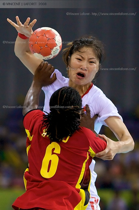 Bing Li  is defended by #6 Bombo Madalena Calandula of Angola in the handball preliminaries.