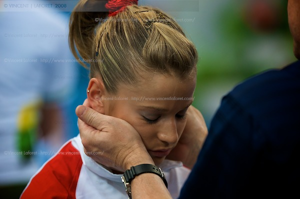 Alicia Sacramone is comforted by her coach Mihai Brestyan. Photograph by Vincent Laforet for NEWSWEEK