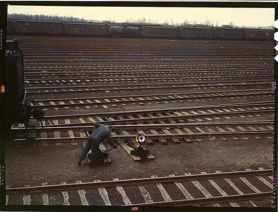 Switchman throwing a switch at Chicago and Northwest Railway Company's Proviso yard. Chicago, Illinois, April 1943. Reproduction from color slide. Photo by Jack Delano. Prints and Photographs Division, Library of Congress