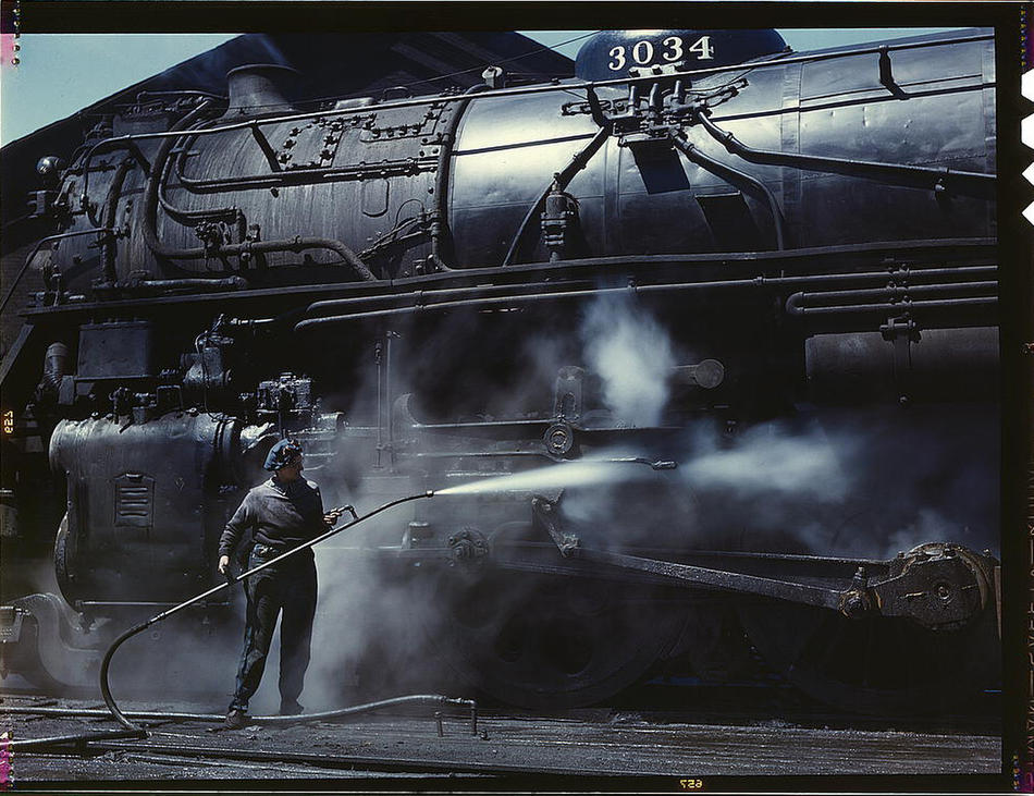 "Mrs. Viola Sievers, one of the wipers at the roundhouse giving a giant ""H"" class locomotive a bath of live steam. Clinton, Iowa, April 1943. Reproduction f"